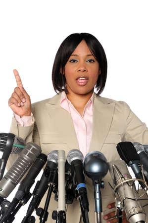 女性記者会見中にマイクの後ろにスピーチを与える 写真素材