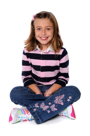 sitting on floor: Portrait of young girl smiling sitting over a white background Stock Photo