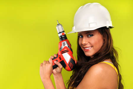 Beautiful young woman with cordless drill