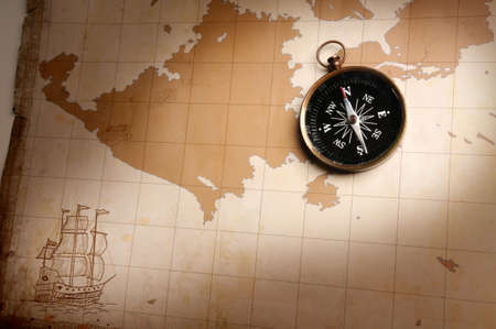 Compass over an old map with directional light photo
