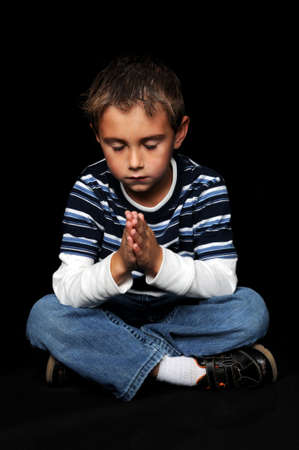 Young boy with hands together praying photo