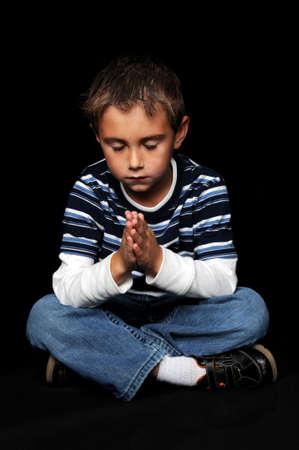 Junge mit Händen zusammen beten