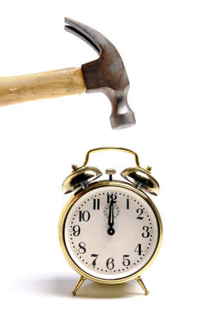 Alarm clock and hammer over a white background