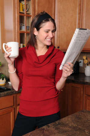 Woman reading the newspaper and smiling photo