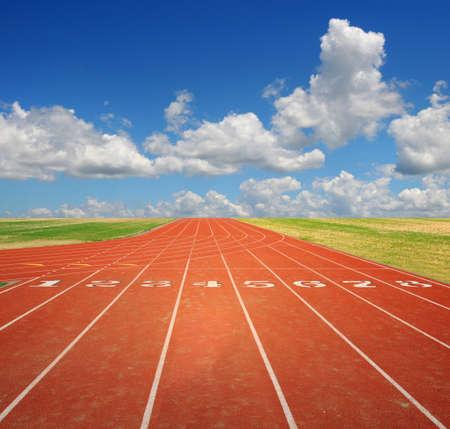 fast lane: Pista de atletismo con ocho carriles con cielo y las nubes