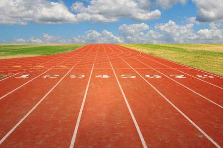 Atletiekbaan met acht rijstroken met lucht en de wolken