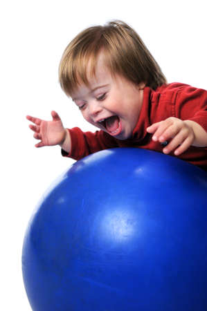 Child with Down Syndrome smiling and playing with ball isolated over a white background. photo