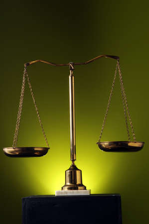 Scales with spotlight over a green background photo