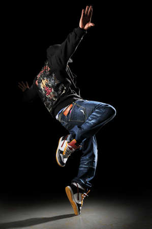 Hip hop dancer performing over a black background