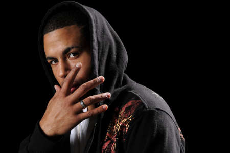 Young African American man with hood and hand in front of face Stock Photo - 7887604
