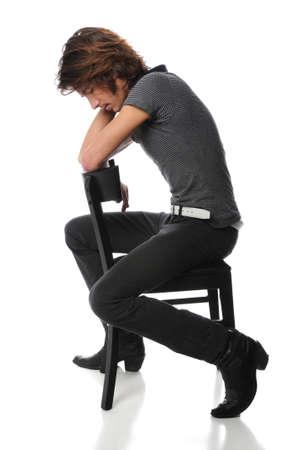Jonge man zit op zwarte stoel met hoofd laag