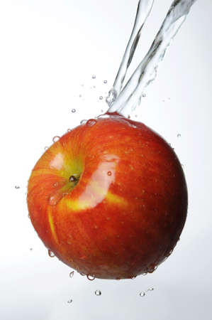 Red apple splashing in water over a light background