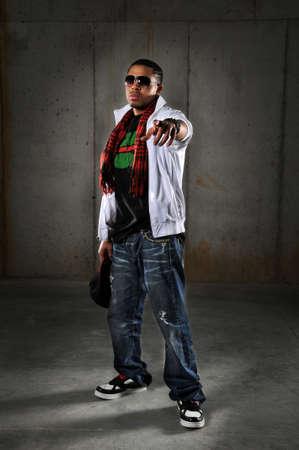 bailarin hombre: Hombre afroamericano de hip-hop apuntando sobre un fondo urbano