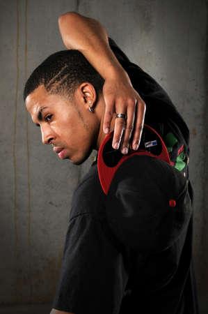 African American hip hop man holding baseball hat Stock Photo
