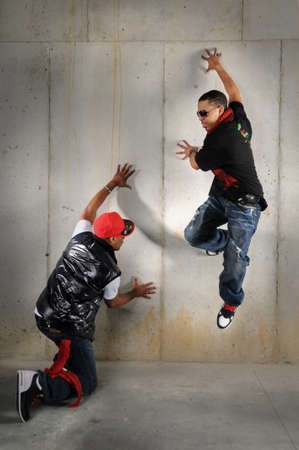 american music: African American hip hop dancers performing against wall Stock Photo