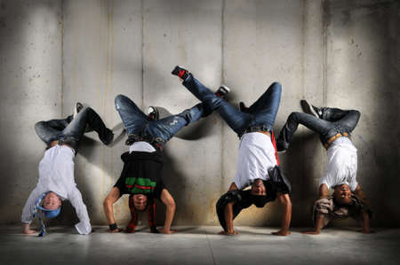 cool down: Hip Hop men performing dance with handstand over grunge background