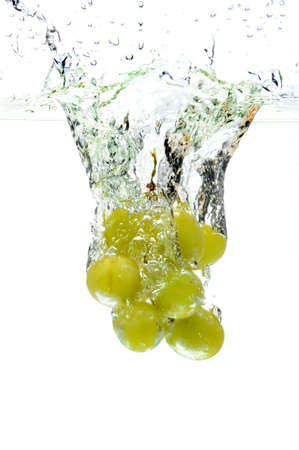 Green grapes splashing into water over a white background