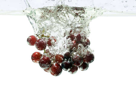 Red grapes splashing into water over a white background photo