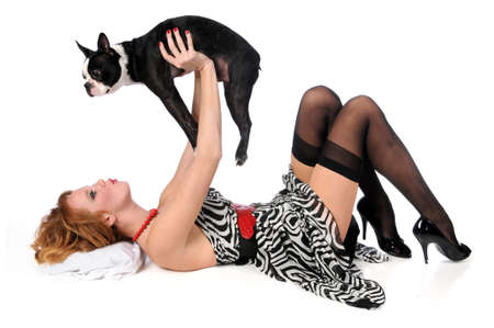 pin up: Pin up girl playing with Boston terrier dog isolated over a white background Stock Photo