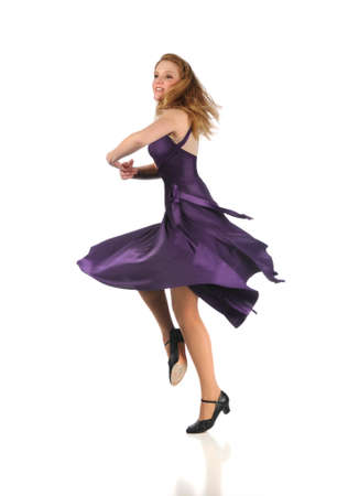 Beautiful woman dressed in purple dress dancing isolated over white background
