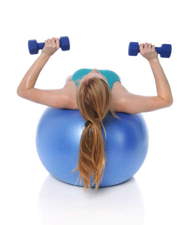 Young woman exercising with dumbbells laying on fitness ball