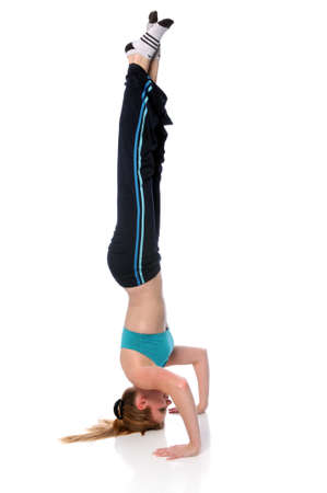 Young blond woman performing headstand overe white background Stock Photo