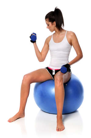 Young woman curling dumbbell sitting on fitness ball photo