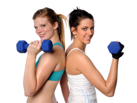 Two women eercirsing with dumbbells isolated over white background photo