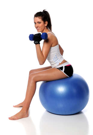 Young brunette working out with dumbbells sitting on fitness ball photo