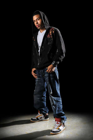 African American hip hop dancer standing over a dark background