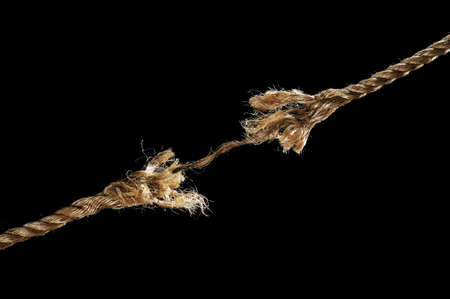 Freyed rope about to break isolated over black background photo