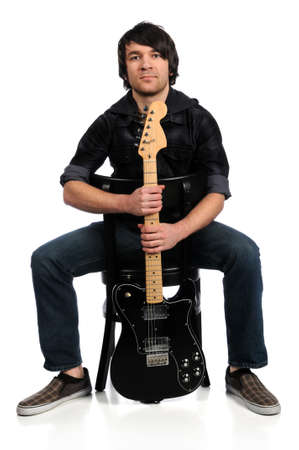 Musician holding guitar sitting on chair isolated over white background