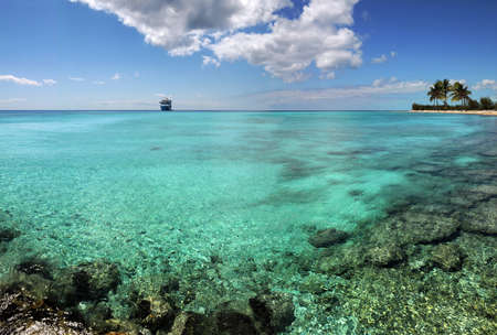 cruises: Tropical paradise with coral reef and cruise ship in the distance - LARGE image stichted from three photographs