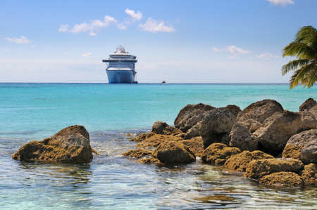 Rocky tropical beach with cruise ship in the background Stock Photo