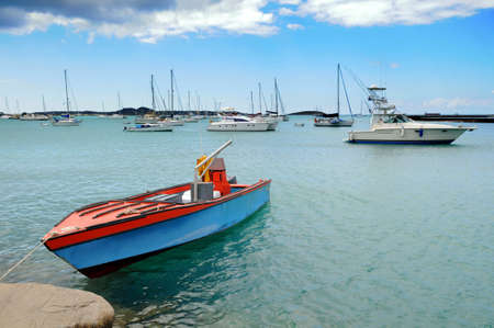 Old boat moored in Saint Martin in the Caribbean, with modern boats in the background photo