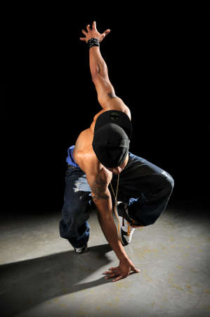 African American hip hop dancer performing over a dark background Stock Photo