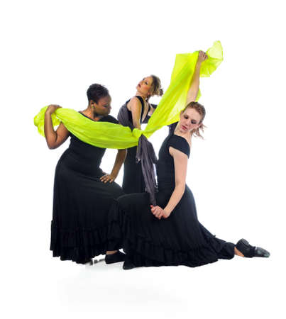 Three women dancers performing with silk cloth isolated over white background photo