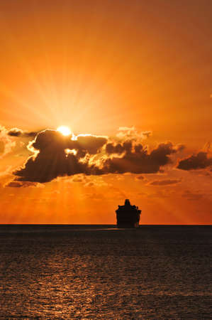 passenger ship: Cruise ship sailing into the sunset with sunburst effect Stock Photo