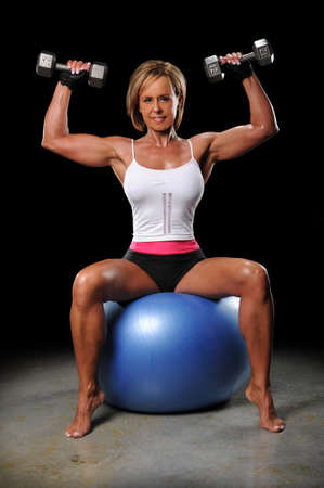Mature woman lifting dumbbels sitting on a fitness ball photo
