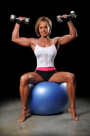 levantar pesas: Mujer madura levantamiento dumbbels sentado en una bola de fitness