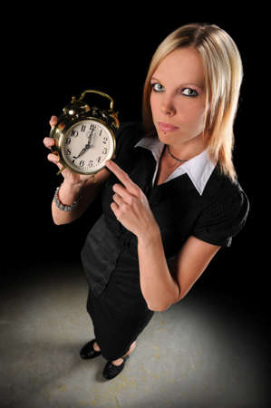 Attractive businesswoman pointing at alarm clock Stock Photo - 7888414