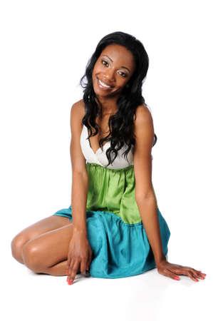 sexy girl sitting: Donna giovane afroamericano sorridente seduto su sfondo bianco
