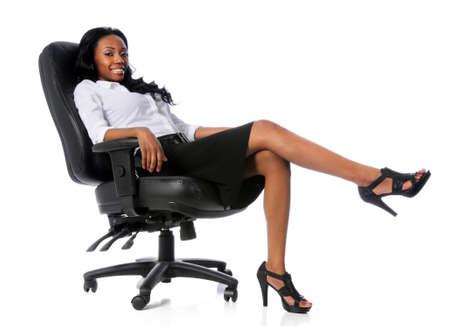 businesswoman suit: Empresaria estadounidense sentado en silla negra aislada sobre blanco  Foto de archivo