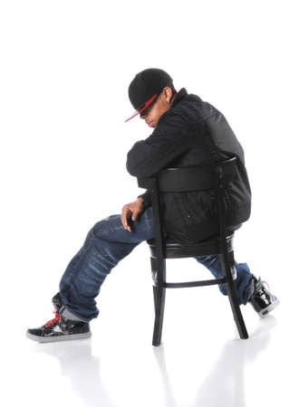 cool guy: African American hip hop man sitting on chair over a white background