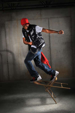 Hip hop dancer performing falling on chair over industrial background