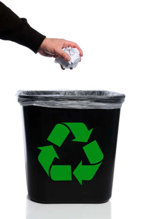 Mans hand placing paper in trash can with recycle symbol