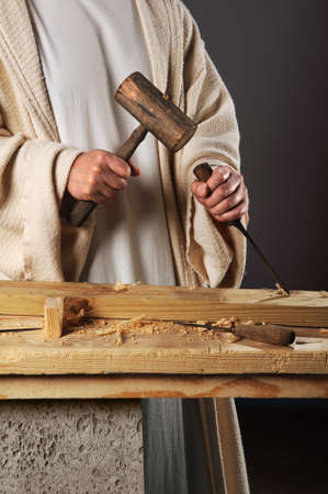 Jesus with mallet and chisel working in workshop  photo