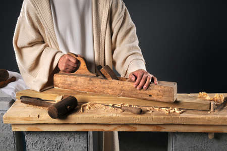 Jesus working with wood plane in carpenters workshop Stock Photo