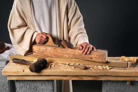 jesus christ: Jesus working with wood plane in carpenters workshop Stock Photo