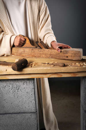 Jesus the carpenter working with a wood plane on a bench Stock Photo